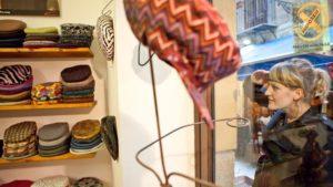 En kvinde kigger på sixpences i hattebutikken La Coppola Storta.